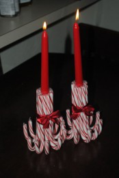 red candles placed into candleholders made of candy canes are great for Christmas decor and you can DIY that