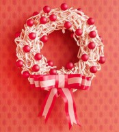 a candy cane wreath with red ornaments and an oversized ribbon bow is a lovely and chic idea of a Christmas decoration for outdoors or indoors