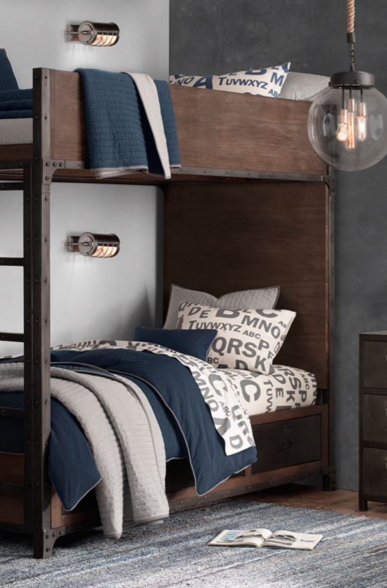 a dark stained industrial bunk bed unit with a ladder with matching metal wall sconces over each bed