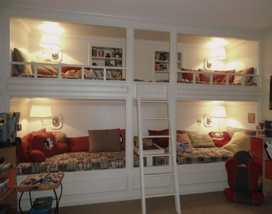 a white vintage bunk bed set of four, cozy wall lamps and a single ladder plus built-in shelves over each upper bed