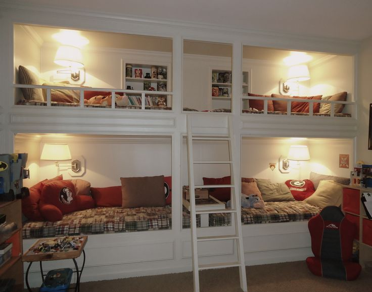 a white vintage bunk bed set of four, cozy wall lamps and a single ladder plus built in shelves over each upper bed