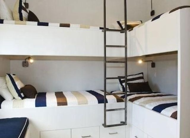 a set of four bunk beds with small wall sconces and a single ladder, no separations between the beds