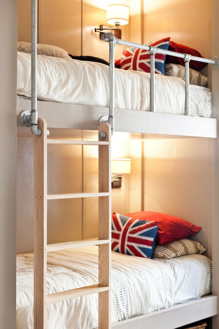 neutral bunk beds and tube railing, wall sconces, a wooden ladder and bright pillows for a colorful accent