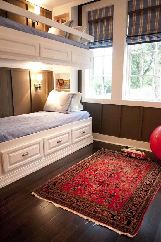 rustic white wooden bunk beds, wall sconces and railing along the upper bed to keep the kid secure