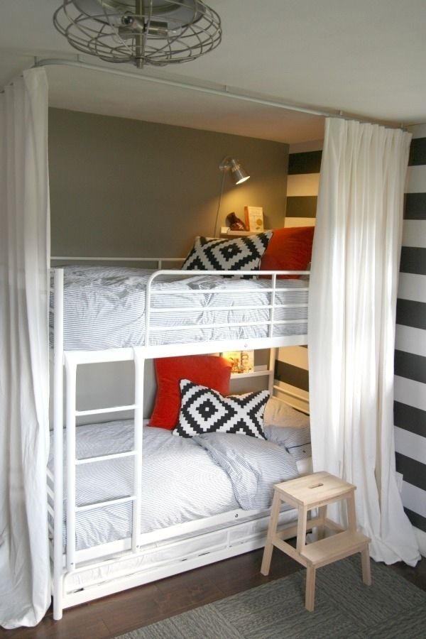 a white metal bunk bed unit for two, wall lamps and shelves plus curtains for cozy sleeping