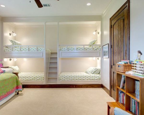 kids' bunk bed units for four, with wall sconces and a single ladder between the bed blocks