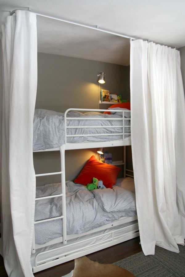 a white metal kids' bunk bed unit with a ladder attached and wall sconces plus curtains to keep the sleeping spaces private