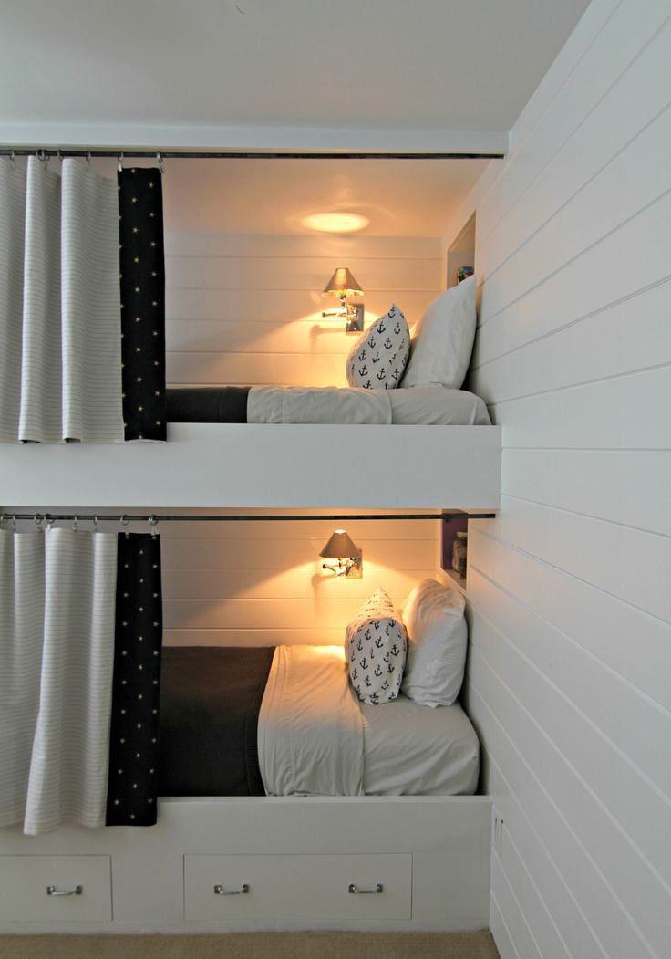 contemporary built in bunk beds with storage drawers, curtains and wall lamps to make the spaces cozier