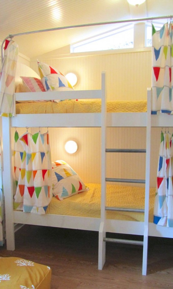 a large white bunk bed unit with a ladder, wall lamps and colorful bedding with various prints