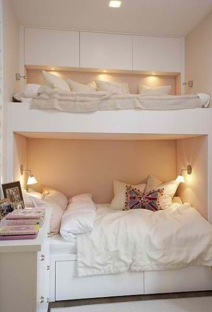 a minimalist white bunk bed unit with a sleek storage space with built in lights and wall sconces over the lower bed