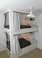 a contemporary bunk bed unit with a metal ladder attached and drawers integrated into the lower bed for storage and curtains for privacy