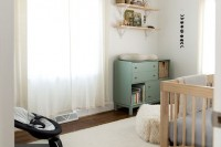 a neutral farmhouse nursery with light-colored furniture, a green changing table, neutral textiles is a very cozy and welcoming room