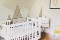 a gender neutral nursery with color block walls and mountains on the wall, a white crib and bright touches is a cozy room
