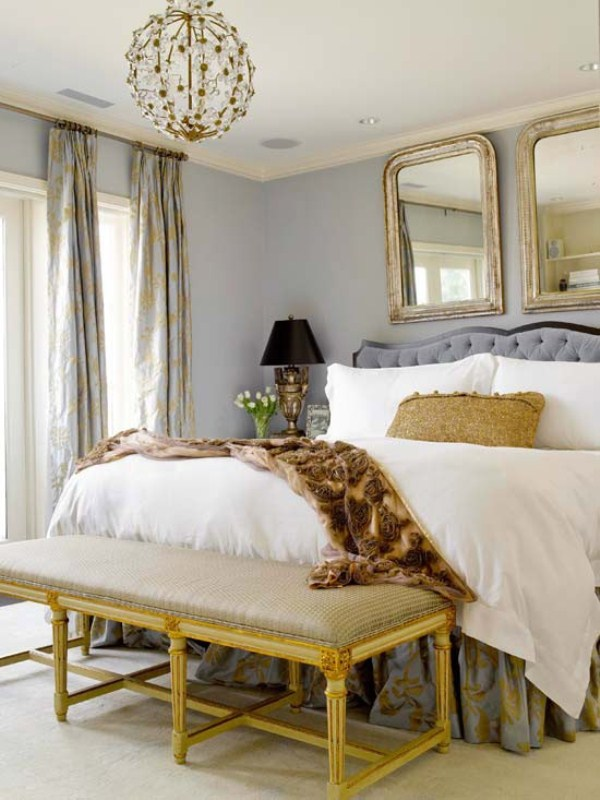 a refined glam bedroom with grey walls, chic mirrors, a globe chandelier, a printed bench and curtains on the windows