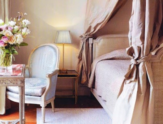 a refined and glam pink bedroom with luxurious textiles, exquisite furniture and lamps plus blooms in a vase