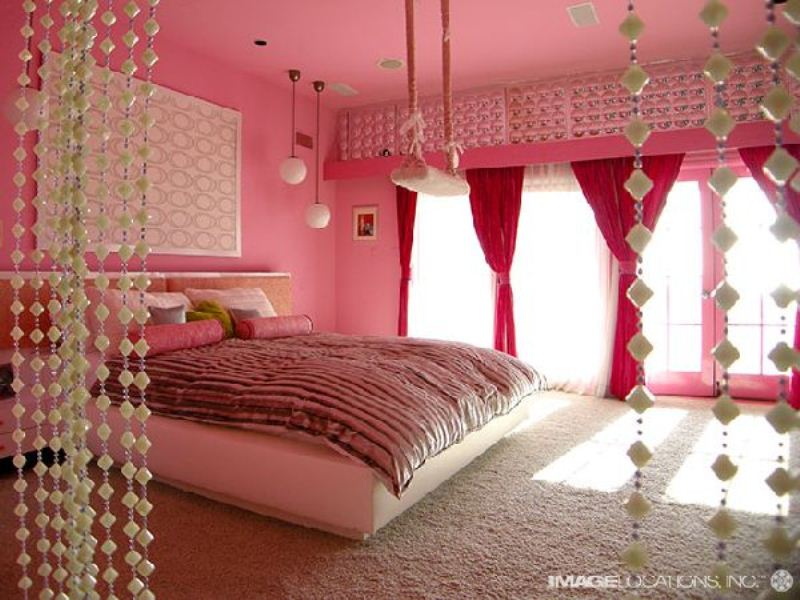 a glam and girlish pink and red bedroom with pink walls, red curtains, hanging crystals and printed textiles