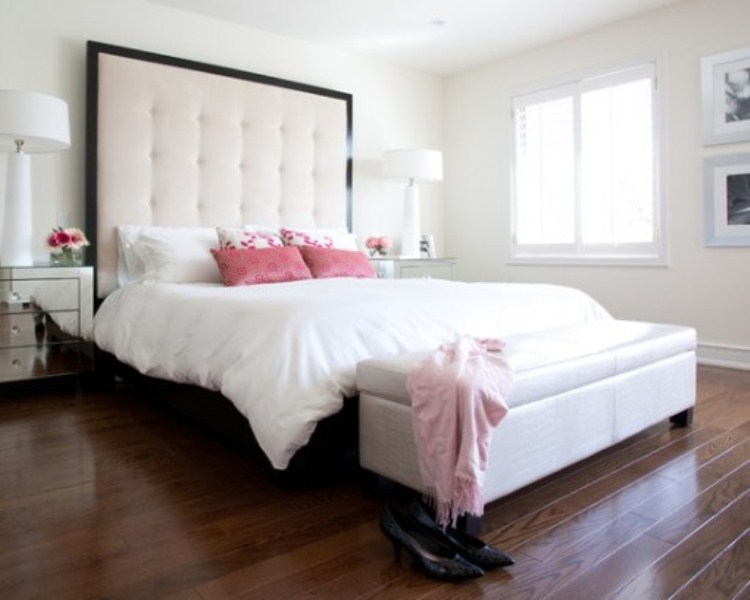 a modern glam bedroom with white walls, an upholstered bed with a statement headboard, a white bench with storage