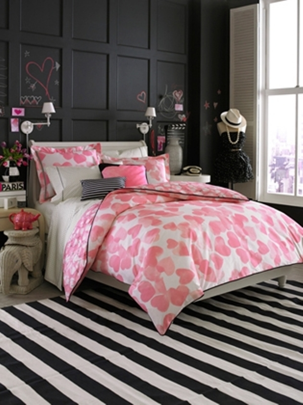 a black, pink and white bedroom with a black statement wall, pink bedding, a striped rug and some girlish decorations