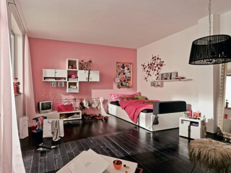 a girlish pink, black and white bedroom with a statement wall, touches of black ro drama and catchy art