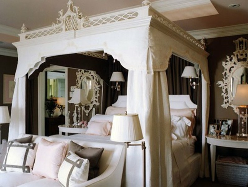 a refined black and white bedroom with a fantastic white carved bed with curtains, ornate mirrors and a chic sofa with pillows
