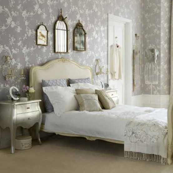 a neutral glam bedroom with a refined bed, refined mirrors on the wall, a chic silver nightstand and feminine touches