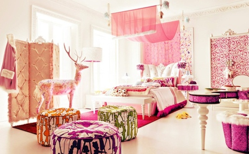 a glam pink bedroom with printed textiles, bright printed ottomans, a pink canopy and screen plus a pink vanity table