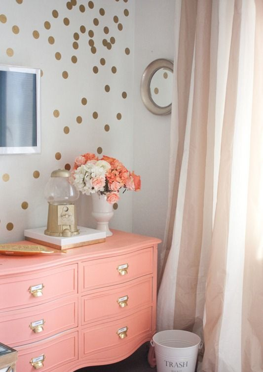 a cute and glam gold polka dot accent wall and a coral dresser with gold knobs, a gold tray and vase is a lovely and playful decor idea