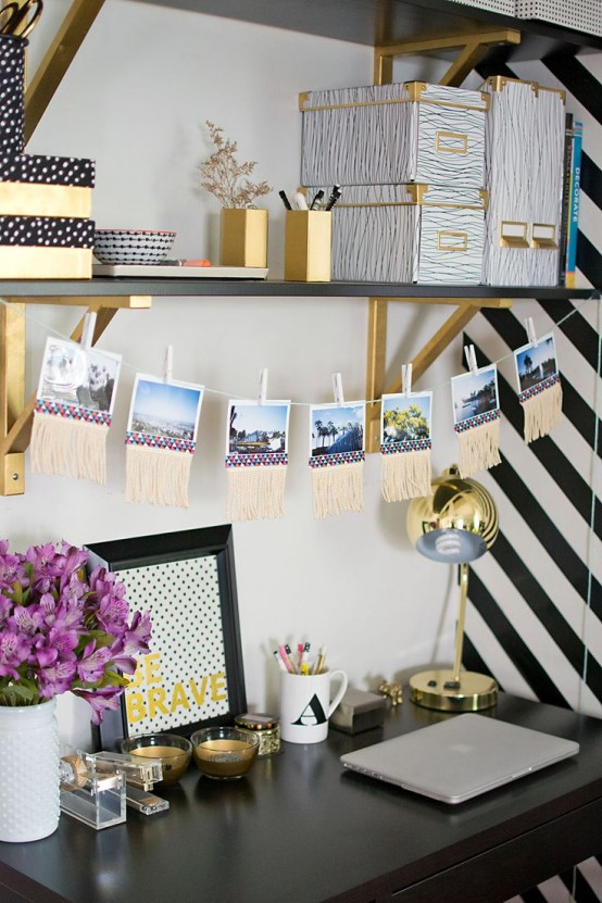 a glam working space in black and white spruced up with gold, with black and gold shelves, gold candleholders, a gold table lamp and some pencil holders is cool