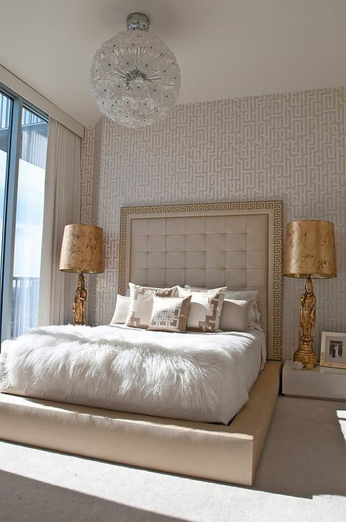 a refined neutral bedroom with catchy wallpaper, a large creamy upholstered bed, neutral and printed bedding, gold table lamps, a floral chandelier is cool