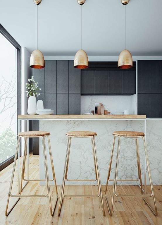 hammered gold pendant lamps and tall gold stools with cork seats make this moody kitchen brighter, cooler and more glam-like