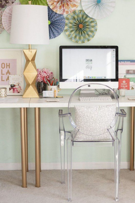 a white desk with gilded legs, a sculptural faceted table lamp give a slight glam-like feel to the home office