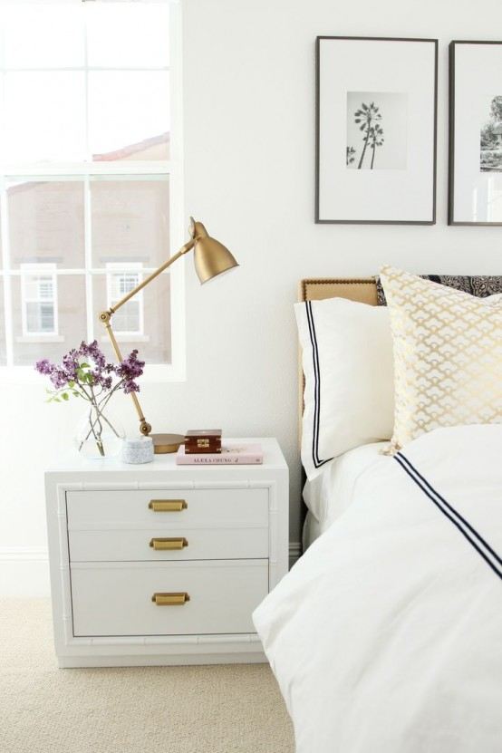 a white nightstand with gold knobs and a gold table lamp add a chic and refined feel to this neutral bedroom