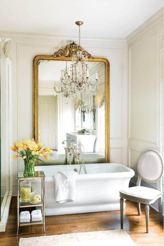 a beautiful vintage-inspired bathroom with an oversized mirror in a gilded frame, a white chair, a tub and a mini glass side table with blooms