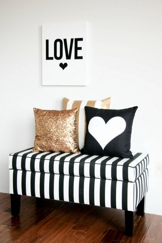 a striped black and white bench, a black and white heart print pillows, a gold sequin and a gold stripe pillow for a cozy glam nook