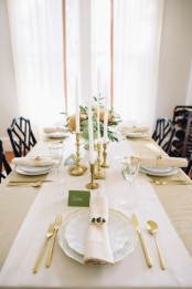 a neutral and refined Thanksgiving tablescape with neutral linens, greenery, warm-colored blooms, candles and gold cutlery for a chic touch
