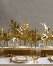 a wooden slab with gilded leaves, gold cutlery and gold touches for a chic and refined Thanksgiving tablescape