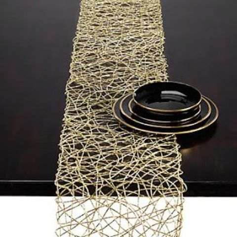 a gold woven table runner and black porcelain with a gold rim can be used for a modern Thanksgiving tablescape
