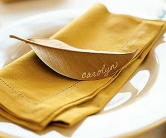 a mustard napkin plus a gold leaf as a place card for a chic Thanksgiving tablescape with a natural feel