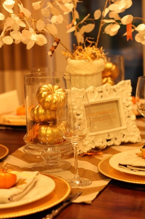 gold chargers, gold pumpkins, gold and white chevron table runners will give a chic and shiny touch to the tablescape