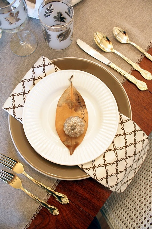 a brown leaf and a gold glitter pumpkin for marking a place setting at Thanksgiving