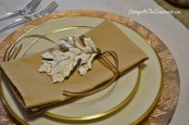 gold rimmed plates, gold napkins, leaves and a charger will add a warm and shiny glow to your fall tablescape