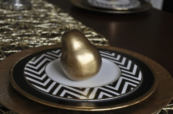 a black charger with a gold rim, chevron plates and gilded pears for a chic and stylish Thanksgiving place setting