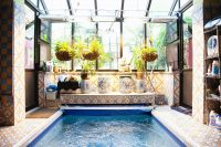 gorgeous tiles and gorgeos vases make the interior of this indoor sunroom pool trully awesome