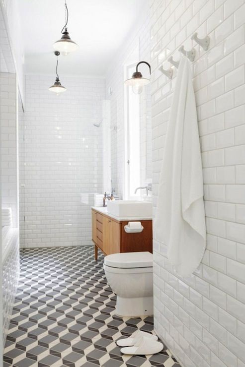 a mid-century modern bathroom with white subway tiles on the walls and black and white geometric tiles on the floor is stylish and cool