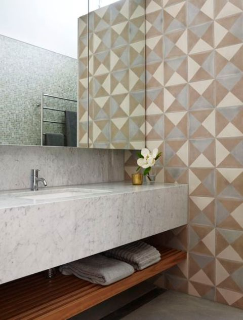a modern bathroom with geometric tiles on the walls, a white stone vanity, blue tiles on other walls is chic