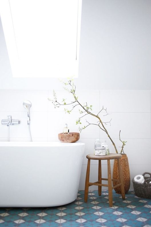 a Scandinavian bathroom with blue geometric tiles on the floor, white large scale tiles on the walls and wooden touches for more coziness