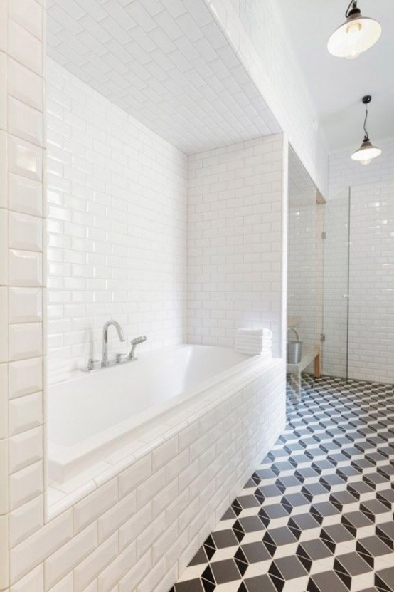 a modern bathroom with white subway tiles on the walls and black and white geometric tiles on the floor is a catchy and chic space
