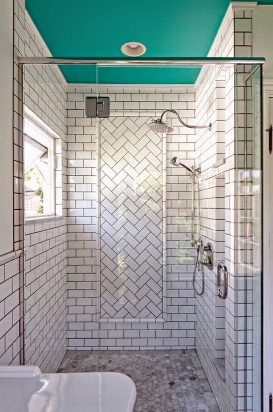 a white subway tile shower space with a herringbone accent and a turquoise ceiling is a bold and cool idea