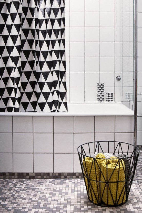 a geometric black and white shower curtain and a geometric wire basket with towels are stylish additions to any neutral bathroom