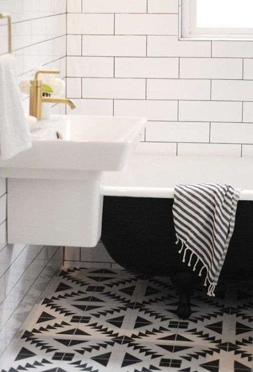 a retro bathroom with a black and white geo tile floor, a black clawfoot tub and a wall-mounted sink for a chic look